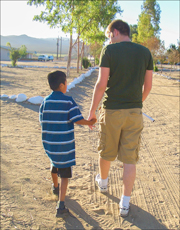 Photo of an adult and child walking hand-in-hand