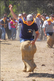 photo showing one of ICC's kids participating in a gunny sack race while attending the 2013 Pathfinder Camporee for Pathfinder clubs in Central America