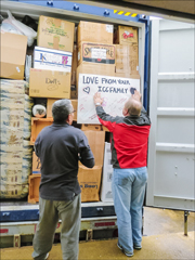 doug congleton and joel reyes place a sign in the patmos container with greetings from the ICC HQ staff