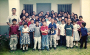 A photo of Julio with his parents and many of the children who are either living in, or formerly lived, in the González home