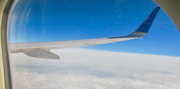 A photo taken through the window of an airliner showing the aircraft's right wing, part of the frame of the window, the azure-blue sky and a solid layer of clouds far below