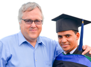 A photo of Rick Fleck with a one of ICC's kids at their high school graduation